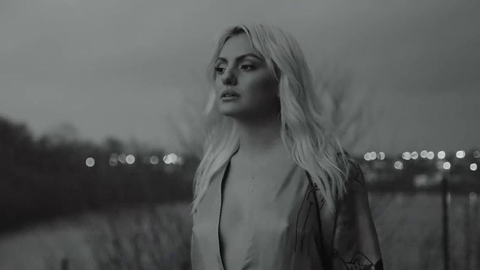 "Still from the ""Obsesii"" music video which sees Alexandra Stan in a black and white filter wearing an open neck-line dress"