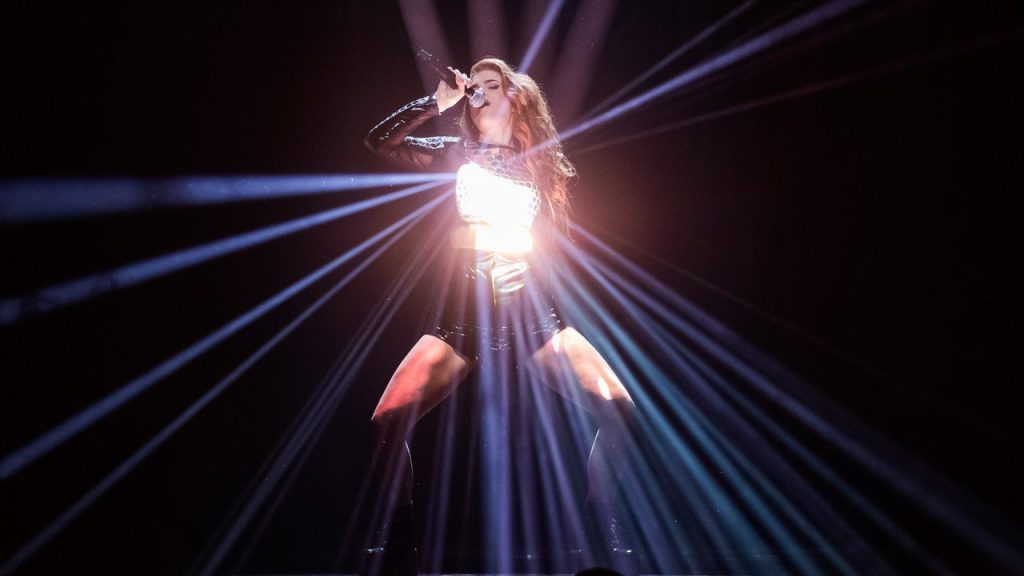 """Dotter performing her song """"Bulletproof"""" on the Melodifestivalen 2020 stage. where she is wearing a mirror-ball-like top that reflects the spotlight beam that's shining down on her"""