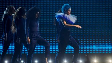 "Eurovision 2020 Australia act Montaigne performing her song ""Don't Break Me"" on the Australia Decides stage, with blue curly short hair, taking inspiration from Pokémon's Mr. Mine"