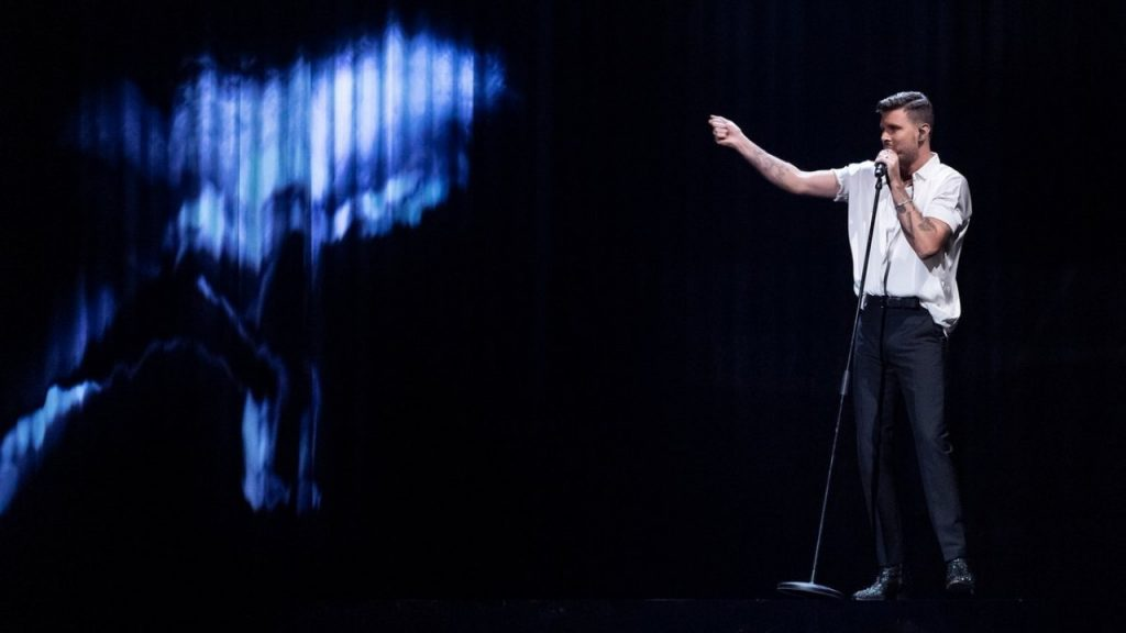 Robin Bengtsson competing in Melodifestivalen wearing a white shirt half-tucked into jeans as he points to a screen to his right which is displaying a figure in motion