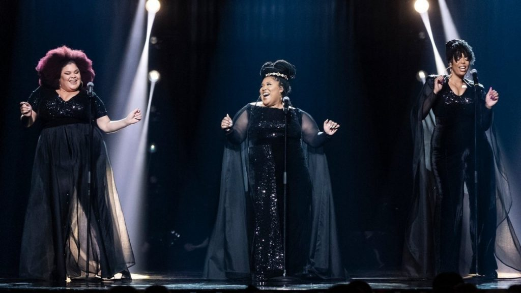 The Mamas on the Melodifestivalen 2020 stage singing in harmony. They are wearing black.