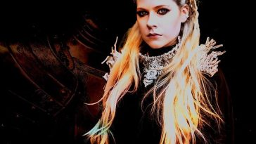 "Avril Lavigne promo photo for her charity single ""Warrior"" wearing a silver neck armour piece with the background displaying a shadow of body armour."