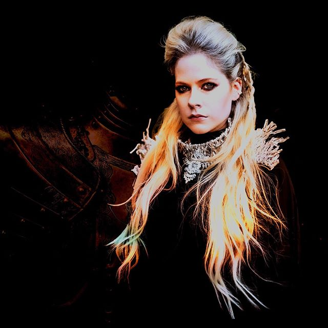 """Avril Lavigne promo photo for her charity single """"Warrior"""" wearing a silver neck armour piece with the background displaying a shadow of body armour."""