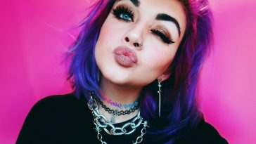 """Bronnie promo pic for """"Over You"""" which sees her winking at the camera, pouting, with her purple hair cut in a bob. She's wearing a black top and chain necklaces with a pink backdrop."""