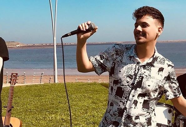 Danny Dearden performing in South Shields wearing a black and white shirt on some grass by the sea, with a microphone in his hand.