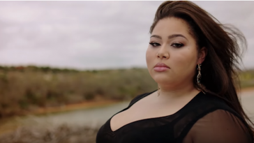 "Still from the ""All Of My Love"" music video which sees Destiny standing on a beach in a black dress, staring at the camera as the wind whips her hair behind her."