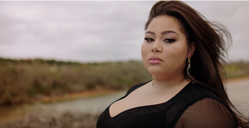 """Still from the """"All Of My Love"""" music video which sees Destiny standing on a beach in a black dress, staring at the camera as the wind whips her hair behind her."""
