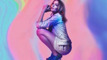 "Lindsay Lohan posing for her ""Back To Me"" single artwork. She is crouching down with her elbows on her knees, she's wearing blue heels paired with a sky-blue top and gold short shorts backed by a blended paint streaks of light blue, pink, yellow and purple."