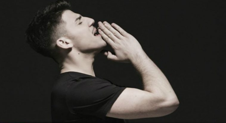 "Cyprus' Eurovision 2020 act, Sandro, in his music video for the song ""Running"" turned to the side, wearing a black t-shirt, with his hands together, raised to his chin."