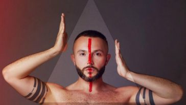 """Vasil topless with a red line down the centre of his face, with his hands on either side of his head in a promo shot for his Eurovision song """"YOU""""."""