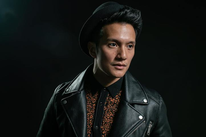 """Vincent Bueno from the """"Alive"""" music video wearing a leather jacket, a black hat, and a netted see-through black shirt."""