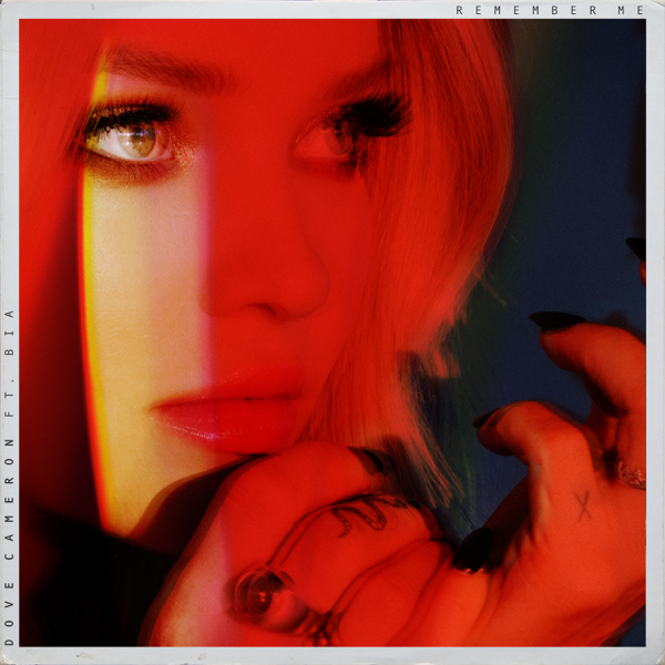 "Dove Cameron single art work for ""Remember Me"" featuring BIA which sees Dove Cameron's face spotlighted with a red filter"