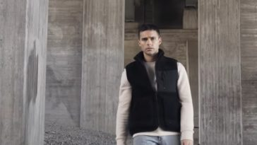 "A still from Eric Saade's music video for ""Glas"" with Eric Saade wearing a black bomber jacket over a cream jumper and light blue jeans standing on gravel amongst grey pillars."