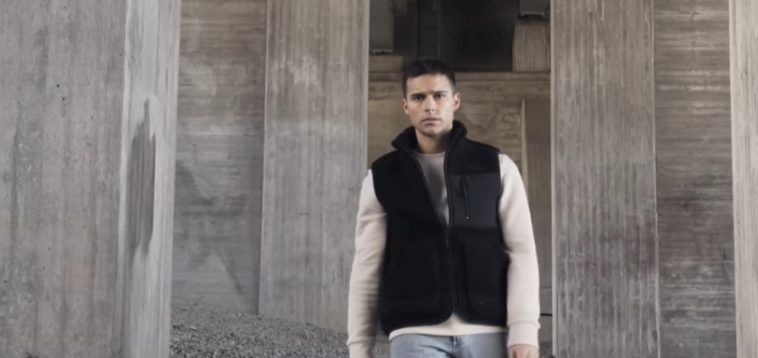 """A still from Eric Saade's music video for """"Glas"""" with Eric Saade wearing a black bomber jacket over a cream jumper and light blue jeans standing on gravel amongst grey pillars."""