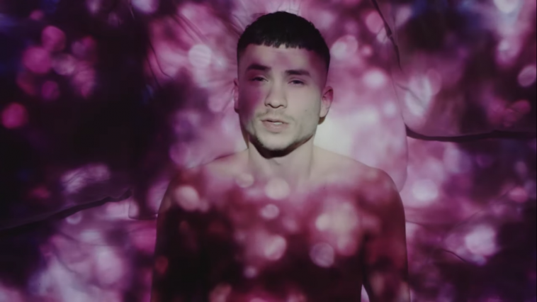 "Still from the ""Talking In My Sleep"" music video which sees Paul Rey lying in a bed with white sheets, topless, as a projector displays pink spotted lights on him and the bed."