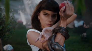 "A still from the ""Not My Baby"" music video which sees INNA staring into the camera holding up a red apple with a black snake wrapped around her arm set within a garden."