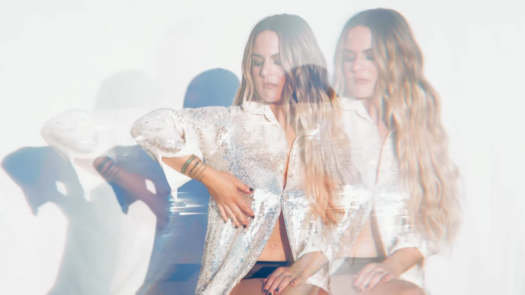 """Still from the music video of """"Lonely Hearts"""" which sees JoJo with her wavy hair over one shoulder, wearing a silver shirt and black pants."""