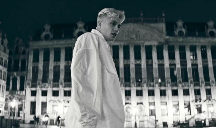 """Loïc Nottet in the music video for """"Mr/Mme"""" wearing a white oversized shirt looking off to the right located in Brussels."""