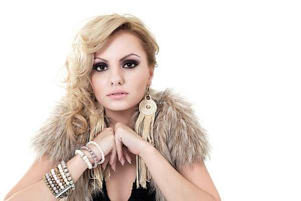 Alexandra Stan promo photo wearing a fluffy shawl around her shoulders with her elbows resting on something in front of her, whilst her blonde hair is wavy, all over one shoulder.