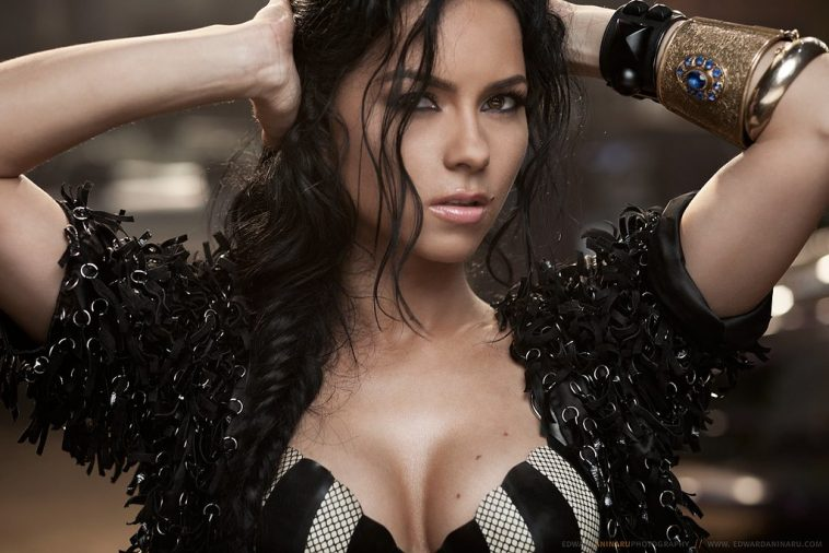 """Music video still from the """"Club Rocker"""" music video which sees INNA in a bra and jacket with her hands on her head."""