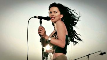 INNA singing on stage into a microphone with the wind whipping her hair behind her.