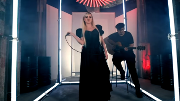 "Alexandra Stan performing in the video for ""Take Me Home"" with Mircea Steriu behind playing the guitar."