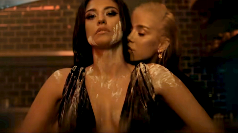 """Still from the """"Como Ay"""" music video which sees Antonia caked in flour with Alina Ceusan behind her, brushing her face near Antonia's neck."""