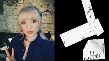 "Leah McFall on the left, wearing a blue shirt-jacket with her highlighted blonde and her fingers up in a peace side, whilst the single artwork cover for ""Rubber"" is on the right which is black with paper strips."