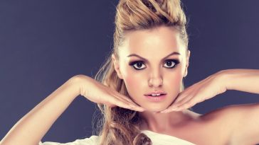 Alexandra Stan framing her face with her hands under her chin and her blonde hair tied up in a ponytail.