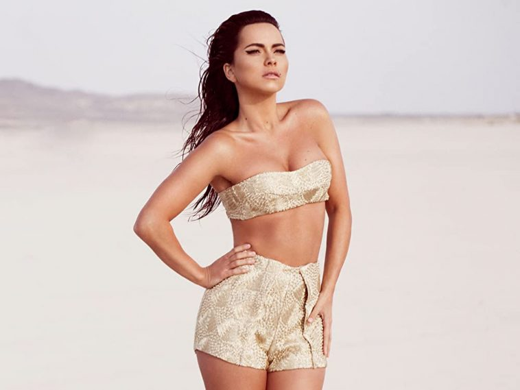 INNA posing on a beach wearing a gold bra and gold short shorts.