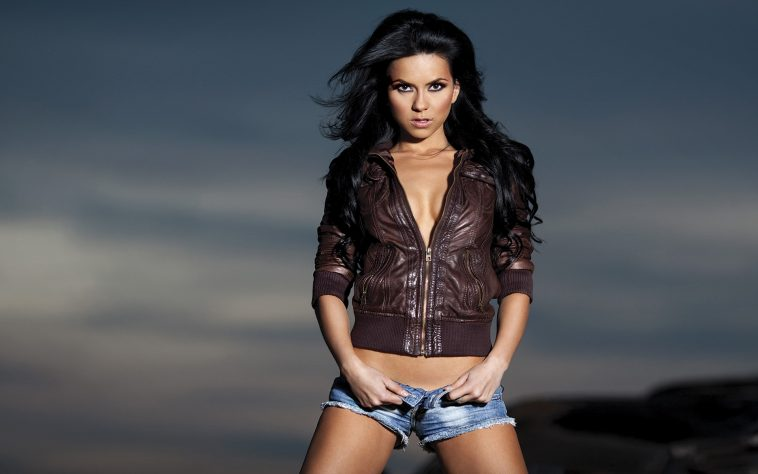INNA wearing a brown leather jacket and some denim short shorts, which she is unbuttoning. The sky is a stormy grey-blue behind her.