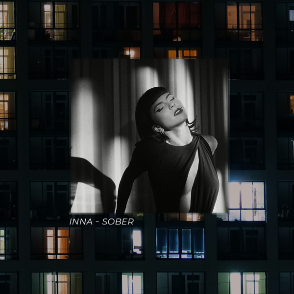 """Single cover artwork for """"Sober"""" which sees INNA wearing a black dress and lying back which is hung as a backdrop over a block of flats."""
