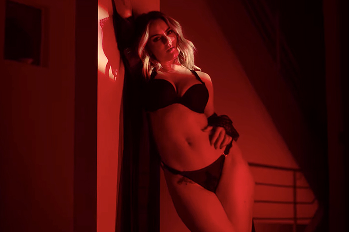 """Snapshot from the """"Comeback"""" music video which sees JoJo in black underwear wearing a see-through robe off her shoulders, leaning against a wall, all in a red filter."""
