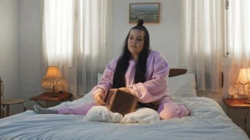 "Netta dressed in pink, on a bed with a music box, singing her new song ""Cuckoo"""