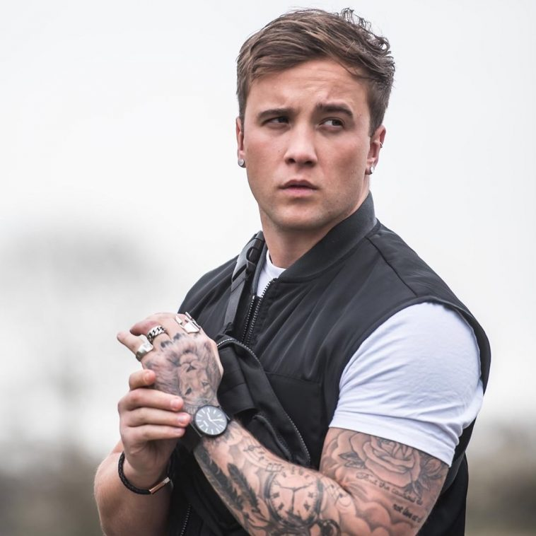 Image of Sam Callahan wearing a white short-sleeved t-shirt with a black bomber jacket, holding his wrist in front of him showing off his tattoo sleeve and his black wrist watch.
