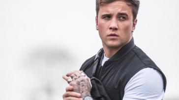 "The single artwork of ""Something To Prove"" which sees Sam Callahan holding his wrist in front of him whilst wearing a short-sleeved white t-shirt and a black bomber jacket."