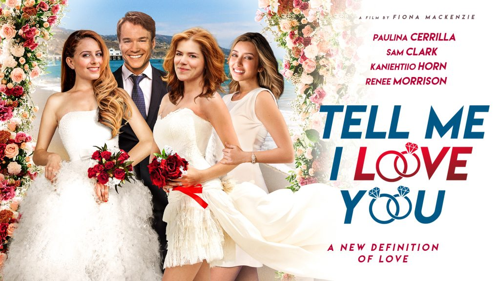 """Promotional image for the film """"Tell Me I Love You"""" which sees an image on the left of the four main characters with Kaniehtiio Horn and Paulina Cerrilla in wedding dresses, Sam Clark in a suit, and Renee Morrison in white. On the right side is the actors' names and the title of the film, with the O's being turned into wedding rings."""