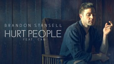 """Brandon Stansell, in promotion of new single """"Hurt People"""" sitting in a wooden chair wearing a blue jacket and a white top."""