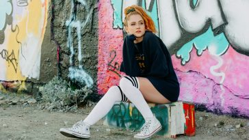 Interview promo picture which sees Janet Devlin in a black jumper and knee-high socks sitting on a concrete block.