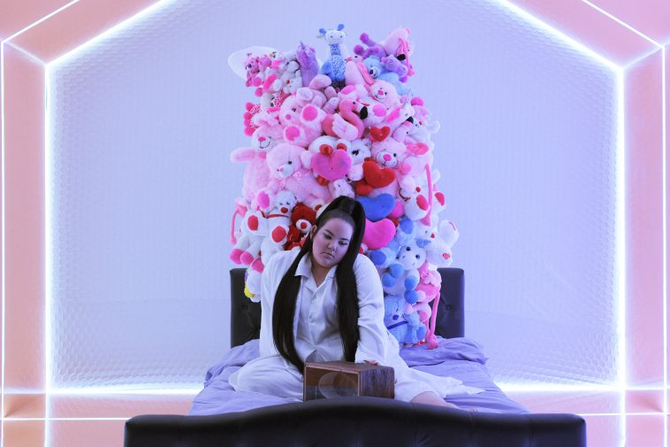 """Still from the """"Cuckoo"""" music video which sees Netta sitting on a bed with her music box in front of her in a neon room."""