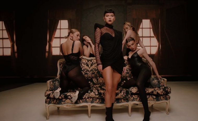"""Music video still from """"VKTM"""" by SICKOTOY, INNA & TAG, which sees INNA standing infront of a sofa with four backing dancers, all dressed in black provocative clothes."""