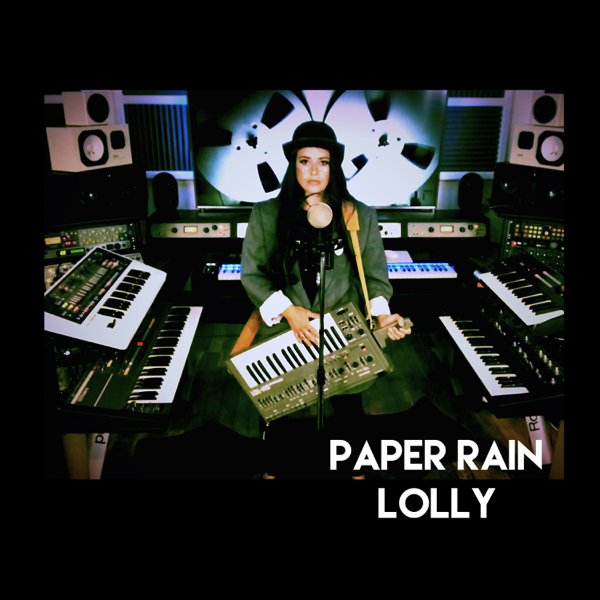 "The single cover artwork for ""Paper Rain"" which sees Lolly in the studio with her keytar and keyboards around her as she sings into a mic."