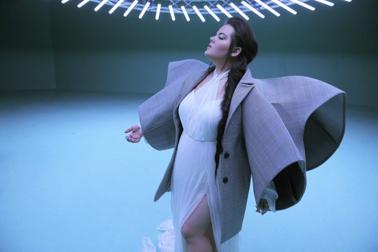 """Still from the """"Cuckoo"""" music video which sees Netta in a white dress with an oversized jacket with wing-like sleeves and her hair over one shoulder."""