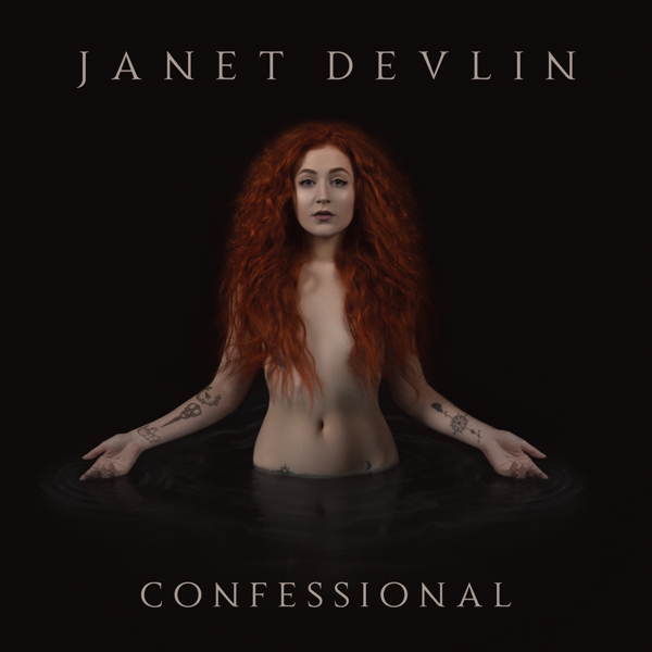 """Album artwork for """"Confessional"""" which sees Janet Devlin in a dark pool of water up to her waist, naked and bare with her red auburn hair covering her chest."""
