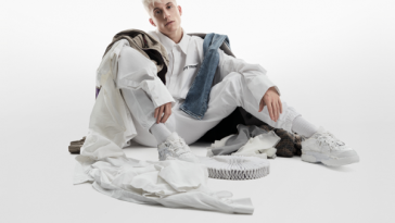 Album artwork for Sillygomania which sees Loïc Nottet sitting with his knees up and his arms on top of his legs, dressed in white with white clothes strewn around him of different colours with a white background.