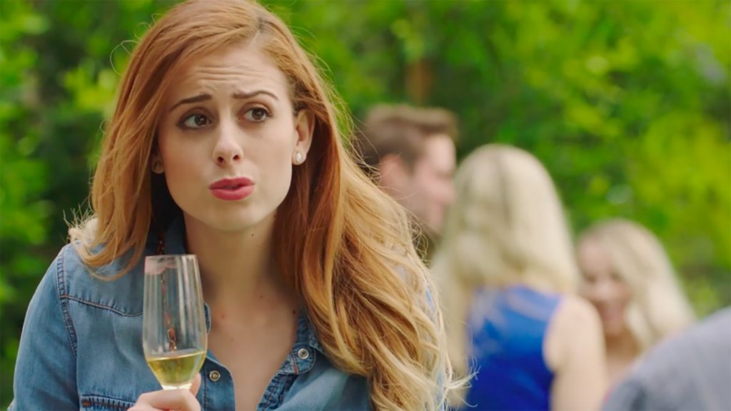 Paulina Cerrilla in the role of Ally, pulling a funny face whilst holding a champagne glass that's half full.