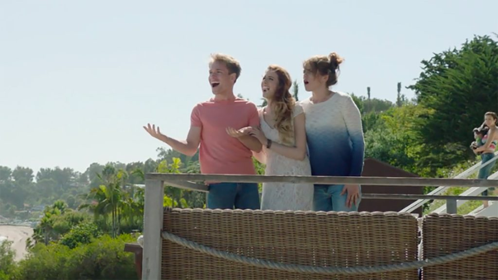 Still from the Tell Me I Love You film which sees Ben, Ally, and Melanie (played by Sam Clark, Paulina Cerrilla, and Kaniehttio Horn, respectively) standing on a balcony overlooking Malibu.