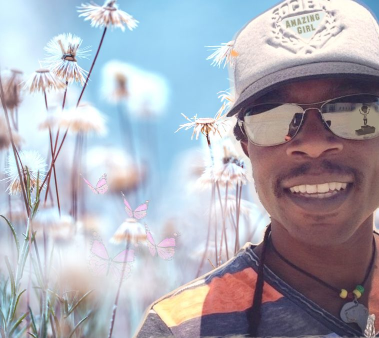 JayQ The Legend wearing a snow-white cap with the title of the song emblazoned on the front. He's also wearing a dark grey and orange striped t-shirt and there's a field of dandelions behind him.