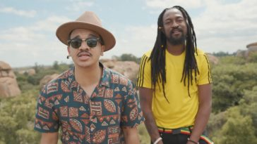 """Still from the """"Midnight Love"""" music video with Jindi on the left sporting a sun hat, sunglasses and an Aztec shirt and Smylie on the right wearing a yellow shirt with black dreadlocks down to his chest."""