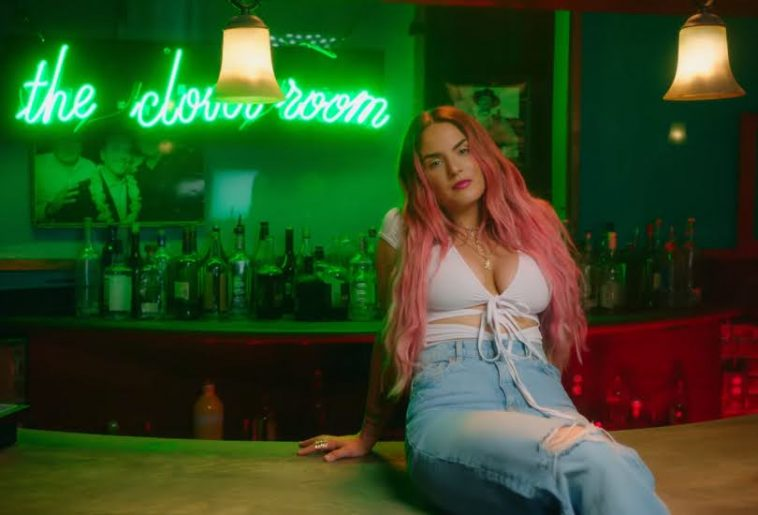 """Still from the """"What U Need"""" music video which sees JoJo with pink hair, sitting on a bar top, wearing a white strap bra and high-waist jeans"""